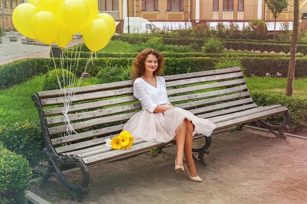 美しい少女が公園のベンチに座って、彼女の横に黄色い花の花束と黄色いボールがベンチに結ばれています。少女は公園のベンチに座っています