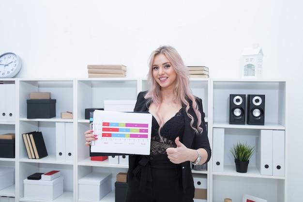Красивая девушка улыбается и держит в руках график развития компании.