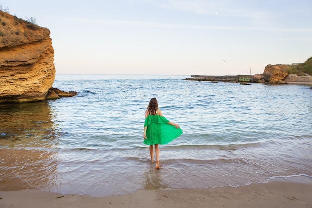 大きな崖と夕日の海の中で、美しい少女が海の近くで回転します。