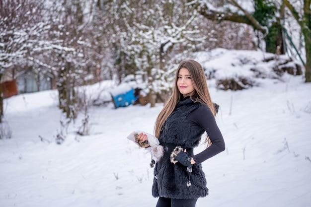 겨울에 정원에 서있는 아름다운 소녀