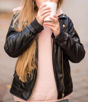 Красивая девушка-подросток в розовом велосипеде и черной куртке держит горячий напиток из белого стакана. фото
