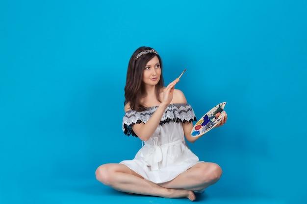 筆とパレットを手にした美しい少女 スタジオの青い表面に白いドレスを着たモデルがポーズをとる