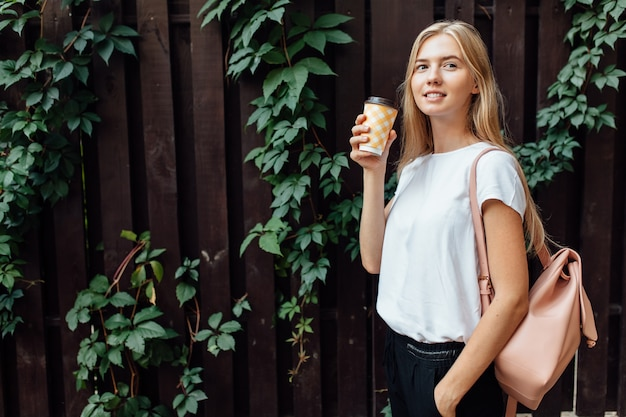 白いtシャツに身を包んだ一杯のコーヒーを持つ美しい少女は、屋外の木製の落葉性壁に立ち、飲み物を飲みます