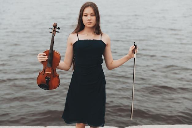 Красивая девушка со скрипкой стоит на фоне воды. азиатская внешность. музыкальная концепция. фото высокого качества