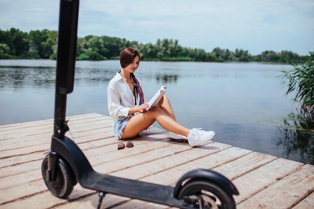 電動スクーターを持った美少女が川沿いの木造橋で本を読んでいます。エコ輸送とヘルスケアの概念。