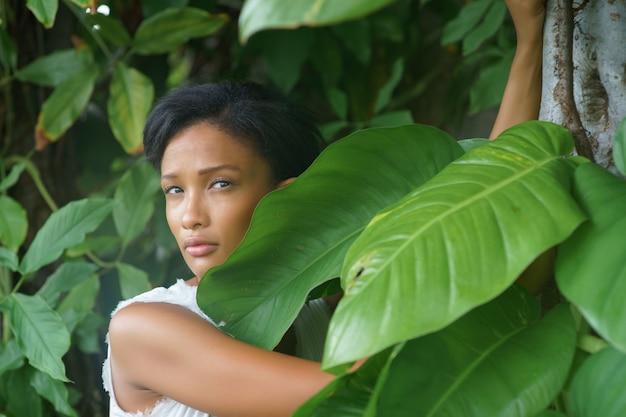 검은 짧은 머리와 흰색 드레스가 큰 아름다운 나무 근처에서 포즈를 취하는 아름다운 소녀