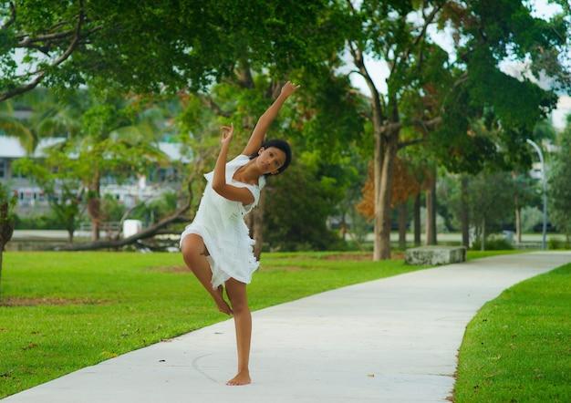 흰 드레스를 입고 춤 포즈에 검은 짧은 머리를 가진 아름다운 소녀