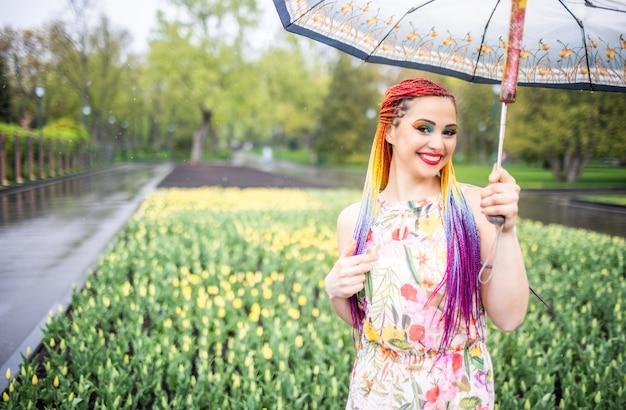 Красивая девушка с яркими разноцветными косами и нарядным зонтиком гуляет по весеннему парку в пасмурную дождливую погоду