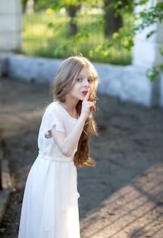8 세 긴 금발 머리를 가진 아름다운 소녀가 흰색 실크 드레스를 입고 신비스럽게 입 근처에 손가락을 쥐고 있습니다.
