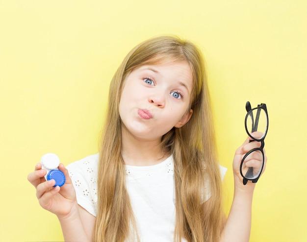 長い髪の美しい少女は、手にレンズと眼鏡の入った容器を持っています。子供の視力問題の概念。黄色の背景。