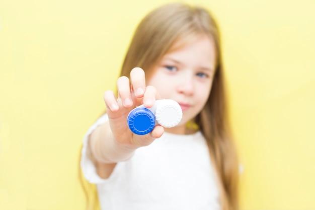 長い髪の美しい少女は、手にレンズの入った容器を持っています。子供の視力問題の概念。黄色の背景。