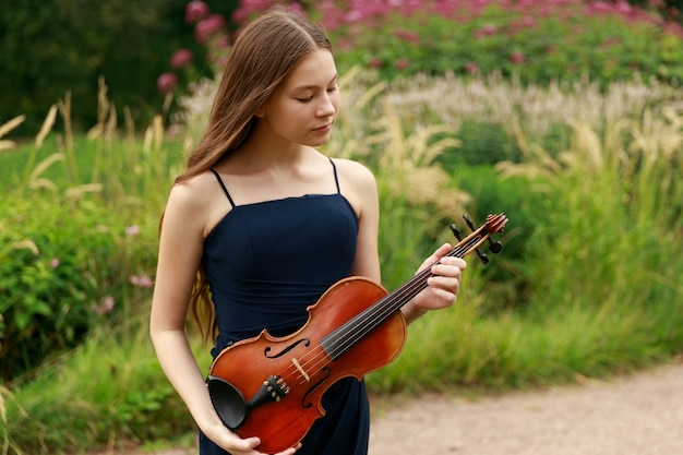 Летом в парке стоит красивая девушка с длинными скрипачками. фото высокого качества