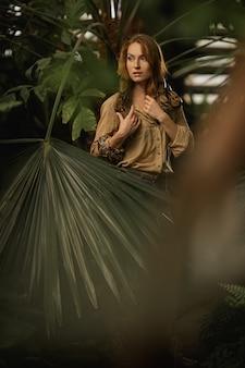 自然のメイクアップと赤い髪の美しい少女は、ヘビとエキゾチックな植物の間のジャングルに立っています。
