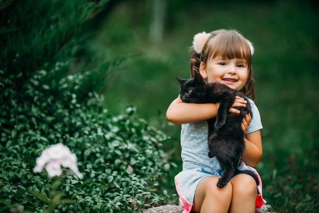 ポニーテールの美しい少女は、黒い子猫を腕に抱いています。アウトドアエンターテインメントと娯楽のコンセプト。