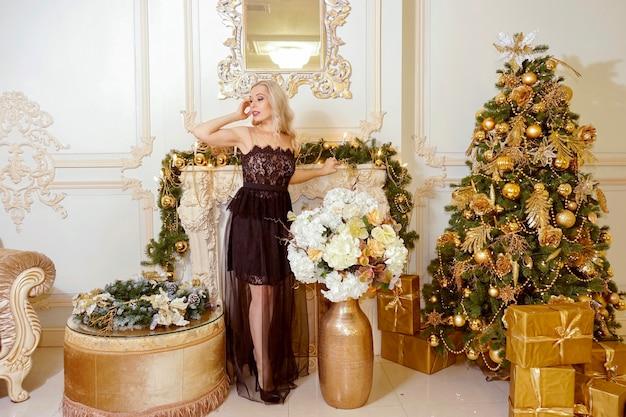 선물을 가진 아름다운 소녀는 크리스마스 트리 근처에 서