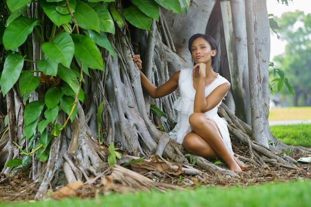 짧은 머리와 흰 드레스가 큰 아름다운 나무 근처에서 포즈를 취하는 아름다운 소녀