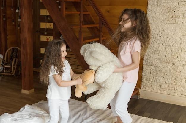 テディベアの美しい女の子は、子供の頃の朝の娯楽の概念のおもちゃで子供を産む