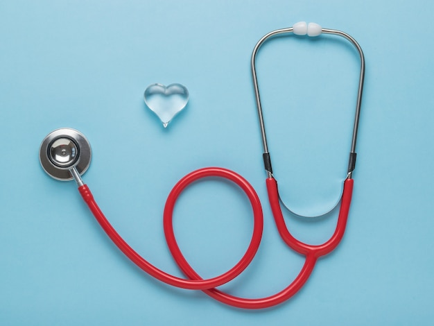 아름 다운 유리 심장 및 파란색 배경에 빨간색 청진 기. 플랫 레이.