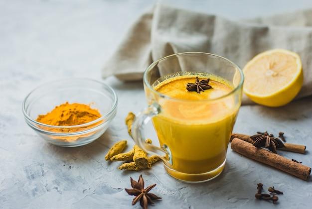 Красивый стакан с золотым молоком, куркумой, специями и лимоном на сером фоне. полезный аюрведический напиток. укрепление иммунной системы. антиоксидант и суперпродукт