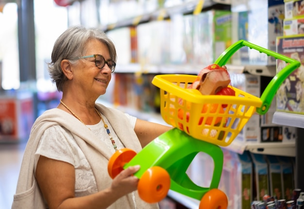 Красивая бабушка рассматривает игрушку, чтобы купить ее внучке. обратите внимание на цену и на то, что товар подходит для ребенка.