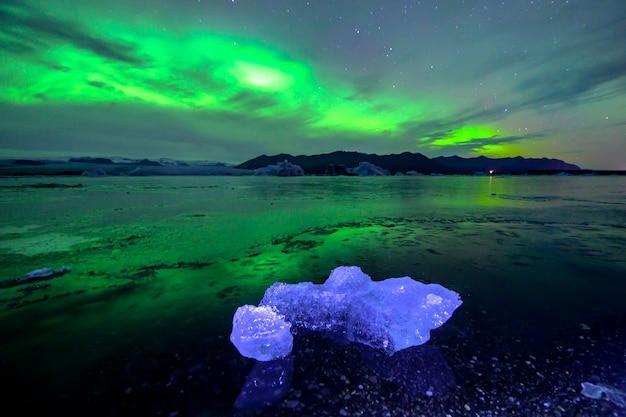 아이슬란드의 jokulsarlon 라군에서 아름다운 녹색과 빨강 오로라 춤
