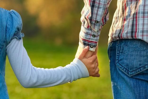 Красивые руки родителей и ребенка на открытом воздухе в парке