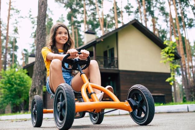 休暇中の美しい幸せな少女は自転車に乗って、夏の森のキャンプで楽しんでいます