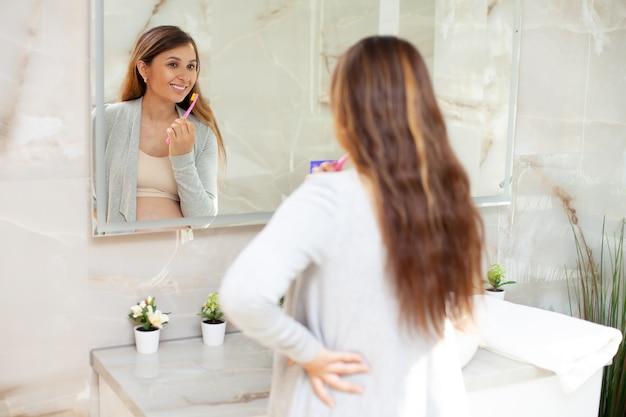 집에서 옷을 입은 아름다운 행복한 임산부는 밝은 욕실에 있는 거울 앞에서 이를 닦습니다. 생활 양식. 아침 저녁 루틴입니다. 위생. 보건 의료. 고품질 사진