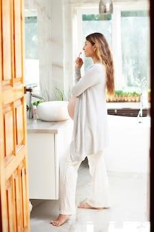 집에서 옷을 입은 아름다운 행복한 임산부는 밝은 욕실에 있는 거울 앞에서 이를 닦습니다. 생활 양식. 아침 저녁 루틴입니다. 위생. 보건 의료. 수직의. 고품질 사진