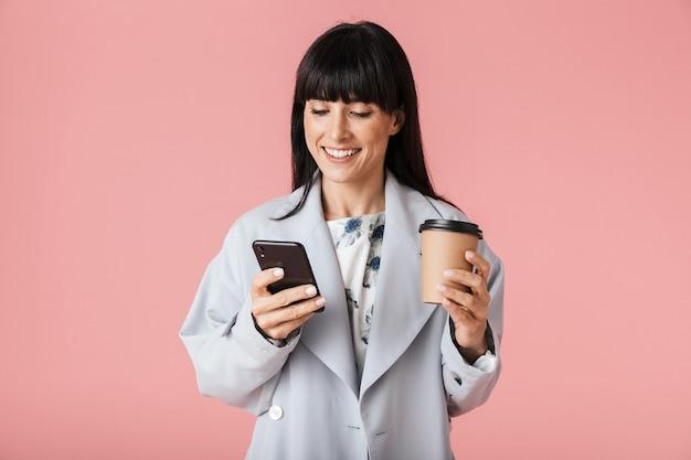 Красивая счастливая женщина позирует изолированной над светло-розовой стеной с помощью мобильного телефона, держащего кофе.