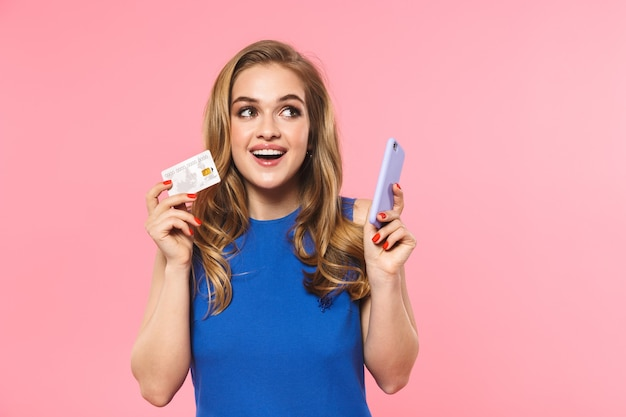 Красивая счастливая молодая симпатичная женщина позирует изолированной над розовой стеной, держащей кредитную карту с помощью мобильного телефона
