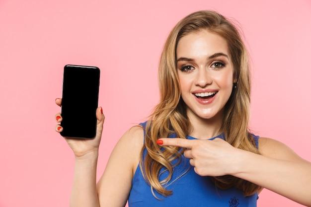 Красивая счастливая молодая симпатичная женщина позирует изолированной над розовой стеной, используя мобильный телефон, показывая пустой дисплей