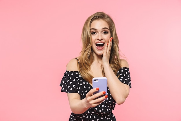 携帯電話を使用してピンクの壁に隔離されてポーズをとって美しい幸せな若いきれいな女性