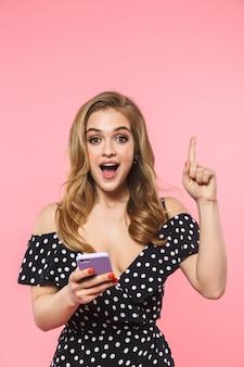 Красивая счастливая молодая красивая женщина позирует изолированной над розовой стеной с помощью мобильного телефона