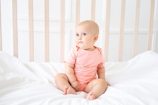 Красивый здоровый жизнерадостный малыш сидит в кроватке с белым постельным бельем, удивленный ребенок