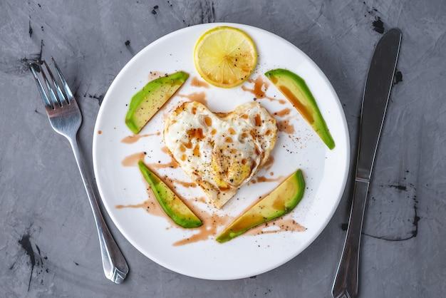 アボカドとレモンのスライスとハートの形をした目玉焼きの美しく健康的なロマンチックな朝食