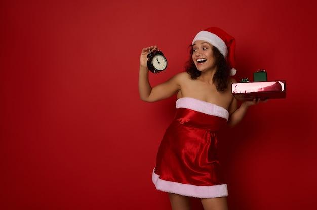 아름다운 히스패닉계 젊은 여성이 크리스마스 선물을 들고 있는 산타 카니발 복장을 하고, 손에 든 알람 시계를 보고 기뻐하고, 붉은 배경 위에 격리된 이빨이 있는 미소를 짓고, 공간을 복사합니다.