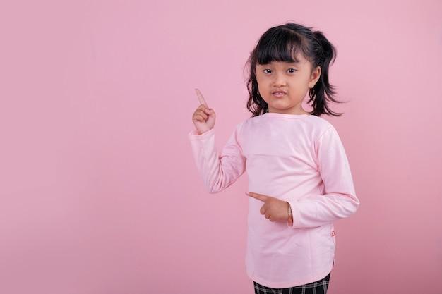 부드러운 분홍색 티셔츠를 입고 무언가를 가리키는 아름다운 아이들