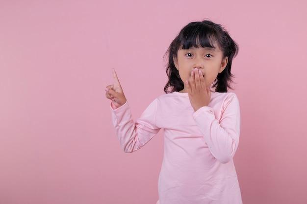 부드러운 핑크색 티셔츠를 입은 아름다운 아이들이 충격과 포인팅 표현
