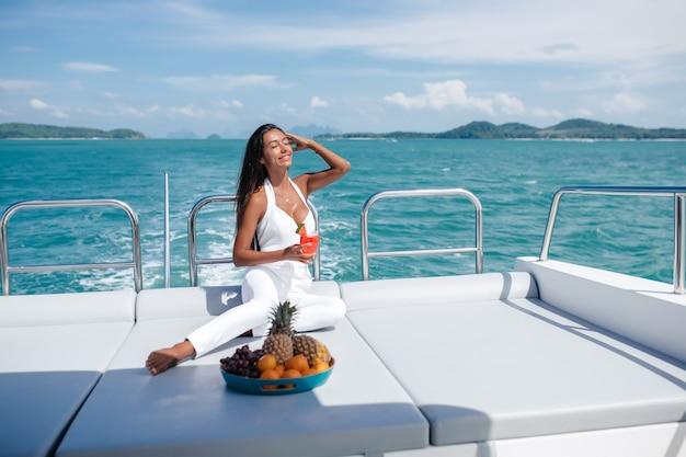 ヨットの白いジャンプスーツを着た美しい女性は、海を背景に、新鮮なスイカを飲み、果物を食べます。背面図