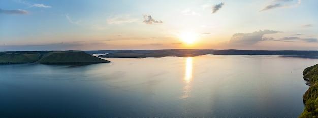 여름날 큰 만 위의 분홍색과 금색 일몰의 아름다운 풍경. 바다의 물에 반사 태양입니다.