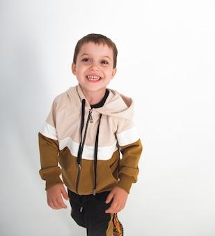 Красивый маленький мальчик в бежевом спортивном костюме на белом фоне