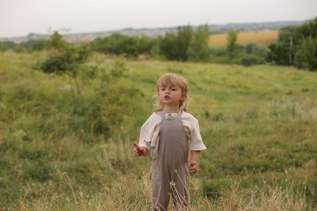 금발 머리와 곱슬머리를 한 아름다운 소년이 강가에서 자연 속에서 쉬고 있다