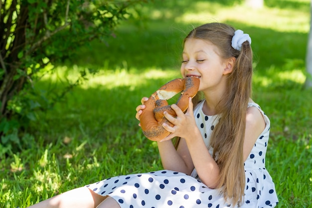 아름다운 소녀는 공원의 잔디에 앉아 롤빵을 먹습니다.