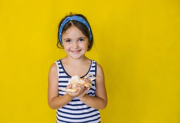 黄色い壁に貝殻を持った美しい少女。