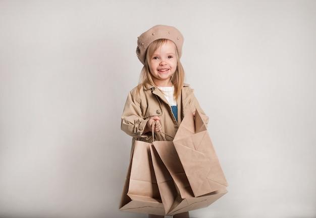 Красивая маленькая девочка в бежевом плаще и берете с бумажными пакетами