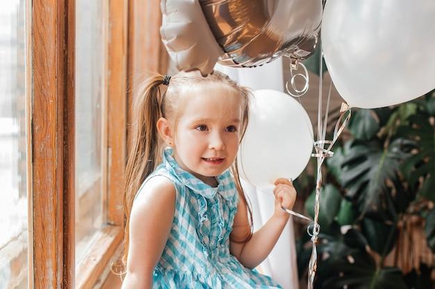 青いドレスを着た美しい少女が白い風船で窓に座っています
