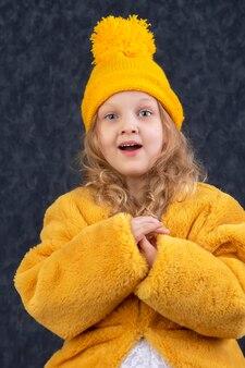 黄色いニットの帽子と暖かい毛皮のコートを着た美しい少女は驚き、賞賛されています。
