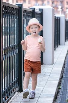 Красивая маленькая девочка в соломенной шляпе ходит и держит мороженое в руке. ребенок высунул язык, хулиган.