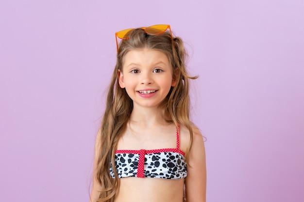 수영복을 입은 아름다운 소녀가 보라색 외진 배경에 포즈를 취하고 있습니다.